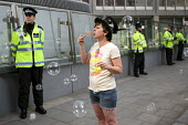 Woman blows soap bubbles at police. End Police Violence. Memorial march for Ian Tomlinson who died on April 1 after being assaulted by a police officer at a G20 demonstration and all others killed by... - Jess Hurd - 23-05-2009