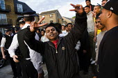 Bengali youth celebrate when the police say the will leave their estate after the Mela, Whitechapel, East London. - Jess Hurd - 2000s,2009,adult,adults,anger,angry,arrest,arrested,arresting,asian,asians,BAME,BAMEs,bigotry,Black,BME,bmes,cities,city,CLJ crime law and justice,communities,community,cultural,DISCRIMINATION,diversi