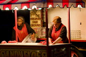 Fairground workers pack up Carters Steam Fair, clearing up the candyfloss stand, Victoria Park. East London. - Jess Hurd - 2000s,2009,apart,at,BAME,BAMEs,Black,BME,bmes,by hand,casual,caterer,caterers,catering,cities,city,cleaning,cleansing,clearing,dismantle,dismantling,diversity,EARNINGS,employee,employees,Employment,EQ