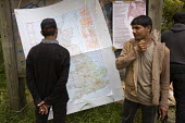 Refugees from Afghanistan look at a map of the UK. No Borders Camp, Calais. France. - Jess Hurd - 26-06-2009
