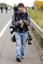 Photographer Justin Tallis with gas mask. No Borders Camp, Calais. France. - Jess Hurd - 2000s,2009,Asylum Seeker,Asylum Seeker,Camp,camps,Diaspora,employee,employees,Employment,eu,Europe,european,europeans,eurozone,foreign,foreigner,foreigners,france,freelance,freelances,french,gasmask,g