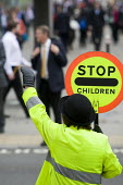 A school crossing patrol officer helps commuters to cross the road as they struggle to get to work during the RMT tube strike. London. - Jess Hurd - 2000s,2009,city urban,cross,crosses,crossing,disputes,EARNINGS,EQUALITY,highway,Income,INCOMES,INDUSTRIAL DISPUTE,inequality,job,jobs,LAB lbr Work,living wage,lollipop lady,lollypop,lollypop lady,low