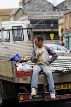 Building worker on lunch break eating a sandwich, Isle of Wight. - Jess Hurd - 29-07-2009