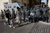 Woman and children walk past police lines, G8 protests, Rome. Italy. - Jess Hurd - 2000s,2009,adult,adults,against,anti,boy,boys,capitalism,capitalist,child,CHILDHOOD,children,cities,city,CLJ,CLJ Crime law and justice,eu,Europe,european,europeans,eurozone,families,family,FEMALE,forc