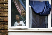 Mother and child look out of their window at English Defence League supporters. Anti-fascist demonstrators and local muslim youths gathered to counter a threatened march by right wing groups outside H... - Jess Hurd - 11-09-2009