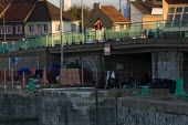Refugees in their temporary home under a bridge before police evict them and destroy their possessions. Calais, France. - Jess Hurd - 2000s,2009,adult,adults,Afghan Afghans,Afghanistan,asylum seeker,asylum seeker,BAME,BAMEs,bigotry,BME,bmes,bridge,CLJ,destitute,Diaspora,DISCRIMINATION,displaced,diversity,equal,equality,ethnic,ethnic