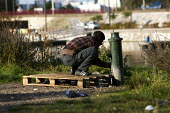 Refugees sleeping rough in Calais are forced to wash at a water pump. France. - Jess Hurd - 2000s,2009,Afghan,Afghan Afghans,Afghanistan,asleep,asylum seeker,asylum seeker,BAME,BAMEs,bigotry,BME,bmes,destitute,Diaspora,DISCRIMINATION,displaced,diversity,equal,equality,ethnic,ethnicity,eu,Eur