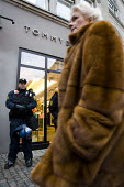 Wealthy woman in a fur coat walks past a Tommy Hilfiger shop protected by riot police. COP15 United Nations Climate Change Conference, Copenhagen 2009, Denmark. - Jess Hurd - 14-12-2009