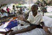 Elderly man with fractured leg is left untreated at an outdoor emergency field hospital. Haiti earthquake. - Jess Hurd - 18-01-2010