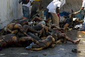 Dead bodies left on the street are shovelled into a truck. Haiti earthquake. - Jess Hurd - 18-01-2010
