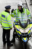 An police Inspector riding a BMW R1200RT motorcycle instructing another officer, police. London - Jess Hurd - 27-02-2010