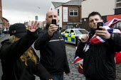 Chris Renton, BNP organiser and EDL member takes a photo and threatens photographer. English Defence League march in Bolton against Islamic Extremism is countered by Unite Against Fascism. - Jess Hurd - 20-03-2010