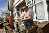 Darren Smith who works as a hospital porter leans his hoover, Jaywick. The seaside village near Clacton-on-sea, Essex was planned by Frank Steadman as a cheap retreat for Londoners in the 1930s and be... - Jess Hurd - 26-04-2010