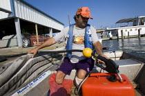 Disabled fisherman filling up his boat with petrol. Grand Isle, Louisiana. USA. - Jess Hurd - 10-08-2010