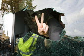EDL leader Tommy Robinson gives the V for victory sign through his smashed up mini bus. Groups of Ajax football club supporters and other anti racists demonstrated against the English Defence League a... - Jess Hurd - 30-10-2010
