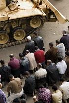 Demonstrators say prayers by a tank. Uprising against Mubarak, Cairo, Egypt. - Jess Hurd - 29-01-2011