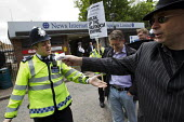 Ian Bone of Class War tries to give a policeman a bribe on a protest outside News International calling for Rebekah Brooks and Murdoch to be arrested for the News of the World phone hacking scandal. W... - Jess Hurd - 08-07-2011