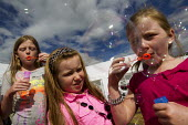 Traveller children blowing bubbles in Camp Constant, the direct action camp supporting travellers against the eviction of Dale Farm, Basildon, Essex. - Jess Hurd - 2010s,2011,activist,activists,against,BAME,BAMEs,bigotry,BME,bmes,bubbles,Camp,CAMPAIGN,campaigner,campaigners,CAMPAIGNING,CAMPAIGNS,camps,Caravan Site,caravans,child,CHILDHOOD,children,DEMONSTRATING,