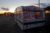 Lady with difficulty breathing. Travellers from Dale Farm on the eve of eviction by Basildon Council. Essex. - Jess Hurd - 2010s,2011,activist,activists,BAME,BAMEs,bigotry,BME,bmes,CAMPAIGN,campaigner,campaigners,CAMPAIGNING,CAMPAIGNS,caravan,caravans,DEMONSTRATING,DEMONSTRATION,DEMONSTRATIONS,DISCRIMINATION,diversity,equ
