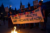 Public Health not Private Wealth banner. Candlelit vigil in Westminster as the Health and Social Care Bill is voted on in the Commons. NHS staff burning placards, London. - Jess Hurd - 07-09-2011