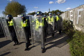 Council officials are escorted by riot police to inspect the site. Travellers from Dale Farm are evicted by bailiffs hired by Basildon Council. Essex. - Jess Hurd - 20-10-2011