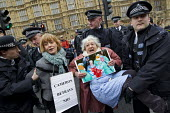 Police carry away UK Uncut protester 81 year old Shirley Murgraff who blocked the road outside the House of Lords against the NHS Bill. Steve Bell, Guardian cartoon placard and Cameron Betrays NHS. We... - Jess Hurd - 27-02-2012