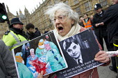 81 year old Shirley Murgraff holding a Steve Bell Guardian cartoon placard and a picture of Nye Bevan. UK Uncut protesters who blocked the road outside the House of Lords against the NHS Bill. Westmin... - Jess Hurd - 27-02-2012