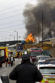 Police and firefighters attend a pallet fire on an industrial estate in Stephanson Street, Newham, East London. - Jess Hurd - 2010s,2012,adult,adults,burn,burning,BURNS,cities,city,CLJ,DIA,Emergency Services,fire,Fire and Rescue,fire brigade,Fire Engine,firefighter,firefighters,firefighting,fireman,firemen,fires,flame,flames