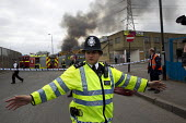 Police officer clears the general public from the area to establish a safe cordon, as firefighters attend a pallet fire on an industrial estate in Stephanson Street, Newham, East London. - Jess Hurd - ,2010s,2012,adult,adults,burn,burning,BURNS,cities,city,CLJ,cordon,DIA,Emergency Services,fire,Fire and Rescue,fire brigade,Fire Engine,firefighter,firefighters,firefighting,fireman,firemen,fires,forc
