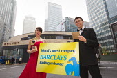 World Development Movement campaigners stage an award ceremony outside Barclays Bank HQ in Canary Wharf handing over a �shame award � won by the bank ahead of its AGM on 27 April. Two glamorous hosts... - Jess Hurd - ,2010s,2012,activist,activists,Bank,BANKS,CAMPAIGN,campaigner,campaigners,CAMPAIGNING,CAMPAIGNS,ceremonies,ceremony,company,DEMONSTRATING,Demonstration,DEMONSTRATIONS,Development,evening,food,FOODS,Mo