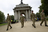 Army soldiers walk through Wellington Arch, Hyde Park Corner, London. Origonally Constitution Arch, a Triumphal arch commemorating Britain's victories in the Napoleonic Wars. The Wellington Arch was b... - Jess Hurd - 27-07-2012