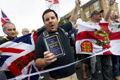 EDL member with a copy of the Qur'an. A march and rally by the English Defence League is stopped by thousands of local anti-fascist protesters We Are Waltham Forest, who blocked the march by sitting i... - Jess Hurd - 01-09-2012