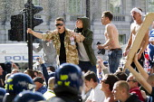 EDL leader Tommy Robinson, on the police barricades in an International Security Assistance Force (ISAF) British army jacket - ISAF are deployed in Afghanistan. English Defence League demonstrate in W... - Jess Hurd - ,2010s,2013,activist,activists,adult,adults,Assistance,barricades,bigotry,CAMPAIGN,campaigner,campaigners,CAMPAIGNING,CAMPAIGNS,Defence,DEFENSE,DEMONSTRATING,Demonstration,DEMONSTRATIONS,DISCRIMINATIO