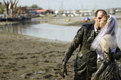 Married couple run the Maldon Mud Race, Essex. Competitors compete to be the first to complete a 400 metre dash over the bed of the River Blackwater. The race is organised by the Lions & Rotary clubs... - Jess Hurd - 05-05-2013