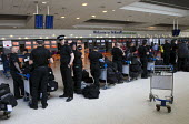 Police check-in for their chartered flight back to London after policing the G8 Summit in County Fermanagh, Befast International Airport. Northern Ireland. - Jess Hurd - 19-06-2013