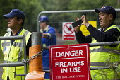 Danger Firearms in use warning sign. G4S Ex Gurkha security guards with CCTV. Mass convergence against Fracking company Cuadrilla Resources who are about start drilling in Balcombe, West Sussex. - Jess Hurd - 25-07-2013