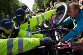 Policeman punches a bicycle wheel into a protesters head. Anti Fracking campaigners join a civil disobedience day in Balcombe in a protest against energy company Cuadrilla Resources who are drilling i... - Jess Hurd - 2010s,2013,activist,activists,adult,adults,against,anti,bicycle,bicycles,BICYCLING,Bicyclist,Bicyclists,BIKE,BIKES,blockade,blockading,blocking,CAMPAIGN,campaigner,campaigners,CAMPAIGNING,CAMPAIGNS,ci