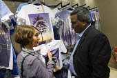 Amirul Haque Amin, President of the Bangladeshi Federation of Garment Workers visits River Island with Rosa Crawford to look at the Banladeshi made t-shirts with Keep away from Fire written on them. T... - Jess Hurd - 2010s,2013,apparel,asian,asians,BAME,BAMEs,Bangladeshes,Bangladeshi,Bangladeshis,Black,BME,bmes,bought,buy,buyer,buyers,buying,capitalism,capitalist,clothes,clothing,commodities,commodity,conference,c