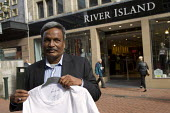 Amirul Haque Amin, President of the Bangladeshi Federation of Garment Workers visits River Island to look at the Banladeshi made t-shirts with Keep away from Fire written on them. TUC, Bournemouth. - Jess Hurd - 2010s,2013,apparel,asian,asians,BAME,BAMEs,Bangladeshes,Bangladeshi,Bangladeshis,Black,BME,bmes,bought,buy,buyer,buyers,buying,capitalism,capitalist,clothes,clothing,commodities,commodity,conference,c