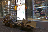 A man sleeping on the streets in front of a cosmetics advertisement and shop. Hong Kong, China. - Jess Hurd - 08-10-2013