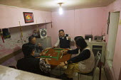 Men play Mahjong, a game with dominos or tiles. Jiaochangkou Hutong is a traditional courtyard residence, most of which are being demolished to make way for new roads and gentrified property developme... - Jess Hurd - 13-10-2013