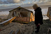 Jackie Connelly with her destroyed home. Badly damaged cliff-top homes after Xavier, the largest tidal surge in 60 years battered the east coast of England. - Jess Hurd - 06-12-2013