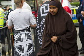 Somali woman walking past a man drapped in a far right Golden Dawn flag. South East Alliance, assorted far right groups are stopped from marching through Cricklewood by anti fascists. The Alliance wer... - Jess Hurd - 14-06-2014