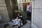 Anti-NATO protestor locks herself by the neck to the entrance of an arms company London office. MDBA is jointly owned by BAE Systems, Airbus Group and Finmeccanica. Protestors from Campaign Against th... - Jess Hurd - 25-07-2014