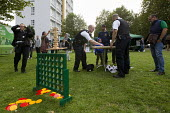 Police playing giant Jenga, Connect 4 and Carrom. Summer Night Lights, a pilot summer violence reduction programme originally launched in Los Angeles to addresses peak offending in anti social hotspot... - Jess Hurd - 2010s,2014,adult,adults,anti-social,BAME,BAMEs,behavior,behaviour,Black,BME,bmes,CLJ,community policing,cop,diversity,Ethnic,ethnicity,fair,force,game,games,MATURE,metropolitan police service,minoriti