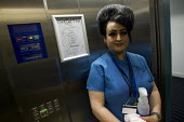 Cecilia - Hotel cleaner on a 12 hour shift with a beehive hairdo and 1960's makeup, Liverpool. - Jess Hurd - 08-09-2014