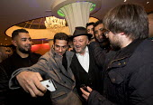 George Galloway MP has a selfie with admirers. Supporters gather to defend Lutfur Rahman, Tower Hamlets Mayor, against financial allegations and smears from Eric Pickles MP. East London. - Jess Hurd - , Protest,2010s,2014,activist,activists,against,BAME,BAMEs,Black,BME,bmes,camera,camera phone,cameras,CAMPAIGN,campaigner,campaigners,CAMPAIGNING,CAMPAIGNS,DEMONSTRATING,DEMONSTRATION,DEMONSTRATIONS,d