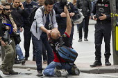 Injured journalist is helped and photographed by his colleagues. Turkish police surround Taksim Square to prevent May Day marches. Istanbul, Turkey. - Jess Hurd - 01-05-2014