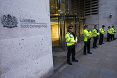 Police guarding the London Stock Exchange. Class War protest against Poor Doors - different entrances for social housing and penthouse accommodation in Aldgate East. The protest marches through London... - Jess Hurd - 01-05-2015