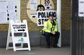 Police officer on duty at a Tower Hamlets Polling Station. General Election. East London. - Jess Hurd - 07-05-2015